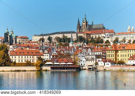 St. Vitus Cathedral And Prague Castle With Orange Roofs Of Historic Buildings Of Mala Strana Reflect