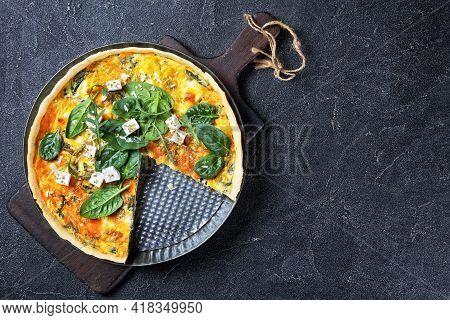 Feta Spinach Parmesan Quiche In A Baking Dish On A Wooden Board On A Grey Concrete Table, Horizontal