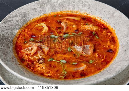 Russian cuisine - Solyanka Soup on dark textured table. Spicy and sour soup with meat slice and vegetables. Ceramic bowl on dark background