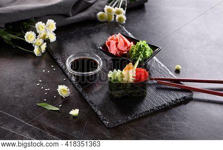 Seaweed wrapped sushi - Gunkan Maki Sushi with Seafood and Tobiko Caviar. Delicious Gunkan Sushi on black slate plate with soy sauce dip. Black stone background
