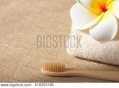 Wooden Bamboo Toothbrush Towel And Flower On Canvas Background, Ecological Body And Dental Cavity Ca
