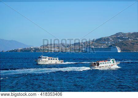 Boat and cruise liner is Aegean sea. Chora, Mykonos island, Greece