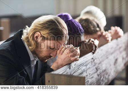 Group Of People Sitting In A Row With Eyes Closed And Praying Together In The Church