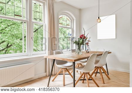 Table With Flowers And Chairs Located Near Windows And Abstract Painting In Light Dining Room At Day