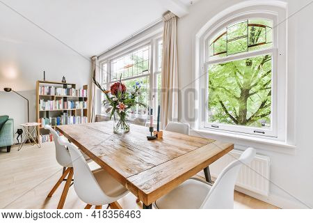 Chairs And Lumber Table With Flowers And Candles Located Near Windows And Bookshelf In Sunlit Dining