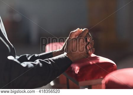 Close-up Of African Man Praying In Front Of The Altar In The Church