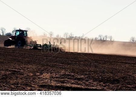 Tractor Plowing Agricultural Field In The Spring . Dust Over The Agricultural Field