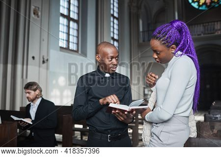 Young African Woman Discussing Bible Together With Priest While They Standing In The Church