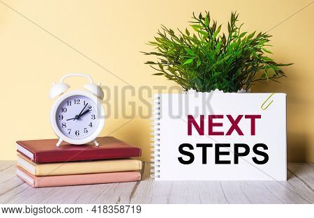 Next Steps Is Written In A Notebook Next To A Green Plant And A White Alarm Clock, Which Stands On C