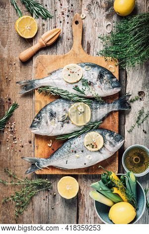 Raw Dorado Fish With Ingredients, Lemon, Herbs, Oil, Vegetables And Spices On Wooden Cutting Board O