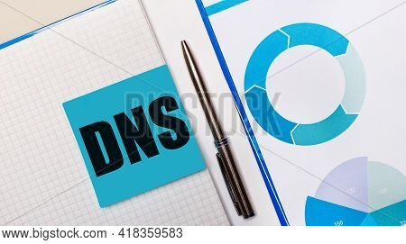 There Is A Pen Between The Blue Sticky Note With The Text Dns Domain Name System And The Blue Chart.