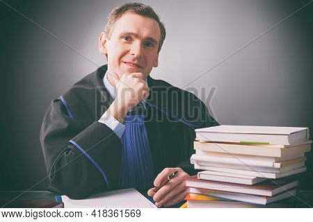 Smiling lawyer in a gown sits at a desk full of books against a dark background