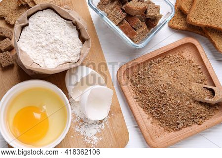 Fresh Breadcrumbs, Flour And Egg On White Wooden Table, Flat Lay