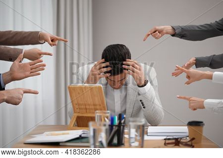 Coworkers Bullying Their Colleague At Workplace In Office, Closeup