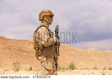 Equipped And Armed Soldier In Camouflage With Rifle In The Desert. Concept Of Military Anti-terroris