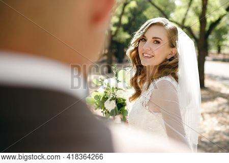 Portrait Of A Smiling Bride Looking At Her Groom On Her Wedding Day. Beautiful Young Woman In A Wedd