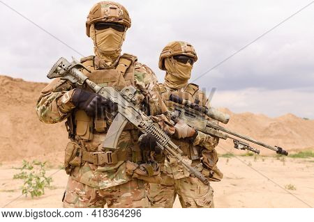 Two Equipped And Armed Special Forces Soldiers Standing In The Desert. Concept Of Military Anti-terr