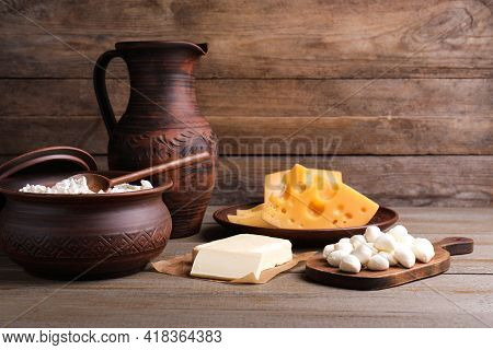 Composition With Dairy Products And Clay Dishware On Wooden Table