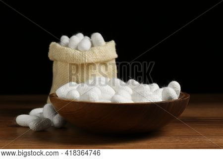 White Silk Cocoons With Bowl And Sackcloth Bag On Wooden Table, Closeup