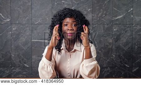 Worried Black Lady In Blouse Holds Crossed Fingers Of Trembling Hands And Smiles With Happiness Sitt