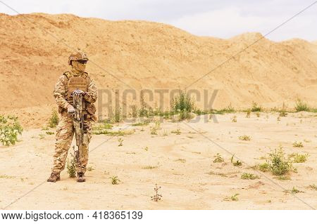 Equipped And Armed Special Forces Soldier, Army Ranger Standing In The Desert With Copy Space. Conce