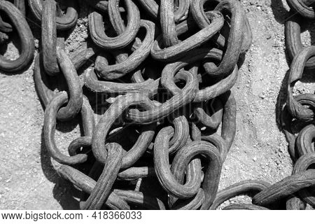 Industrial Iron Chain. Old Iron Chains in a pile on the ground with rust and dirt. In Black and White.