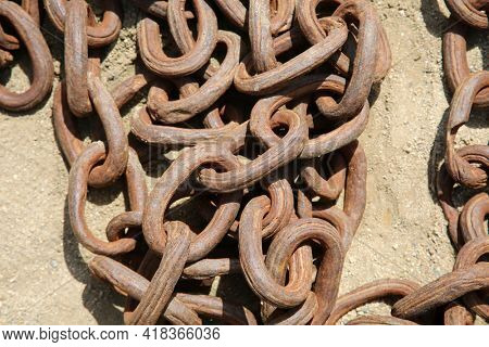 Industrial Iron Chain. Old Iron Chains in a pile on the ground with rust and dirt.