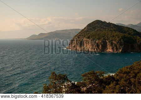 Magnificent View Of Rock With Green Trees Near The Water Of Sea Coast