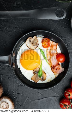 Scrambled Eggs In Frying Pan With Pork Lard, Bread And Green Feather In Cast Iron Frying Pan, On Bla