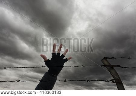 Two Rows Of Barbed Wire, A Fence Post And A Hand, With Storm Clouds In The Background. Immigration,