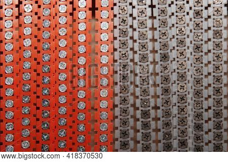 Red, Gray Ribbon Rows Of Metal Screws With Steel Threads.chrome Self-tapping Screws As The Backgroun