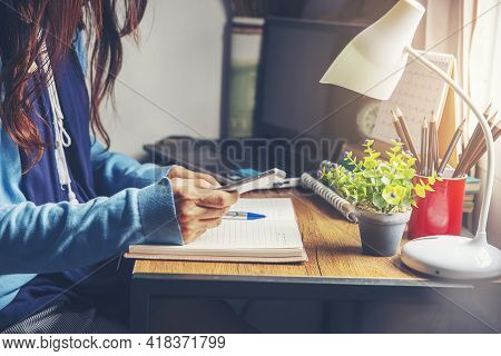 Working From Home Concept. Hand Of Planner Using Phone And Write Daily Agenda On Calendar Book. Woma