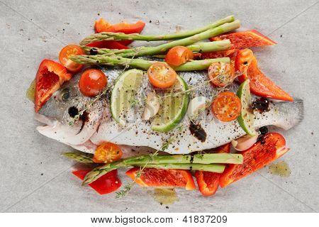 Dorade with vegetables prepared for roasting in culinary paper bag
