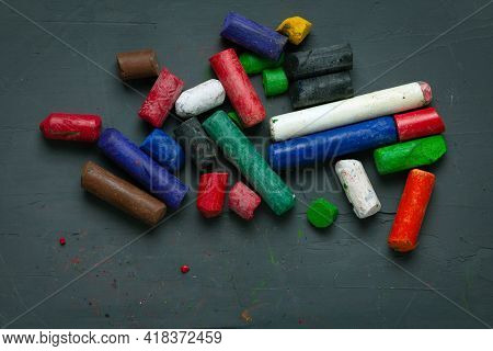 Collection Of Old Colorful Wax Crayons On A Dark Background. Artistic Background For Designs And Pos