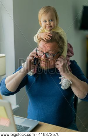 A freelance man father tries to work at home on a computer on the Internet and sits with a small child who prevents him from doing business