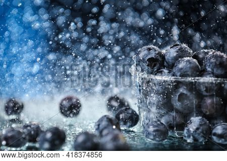 Big Blueberries In A Plastic Box Closeup Under The Water Drops In A Dark Blue Background. Healthy Li