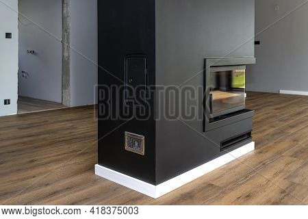 A Modern Fireplace With A Closed Combustion Chamber Standing In The Living Room, Painted Black, With