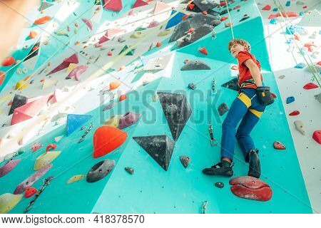 Teenager boy at indoor climbing wall hall starting climbing. Boy using climbing harness and chalk powder when somebody belaying him from floor. Active teenager time spending concept image.