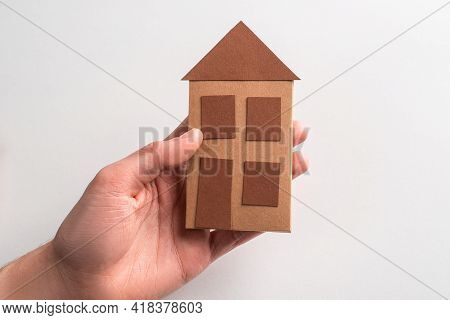 Close-up On A Hand Holding A Paper House On White Background