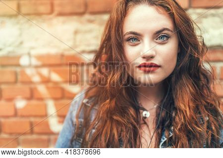 Fashion portrait of red curled long hair caucasian teen girl with applied red lipstick lips with blue eyes with a red brick wall background. Natural people\\\'s beauty concept image.