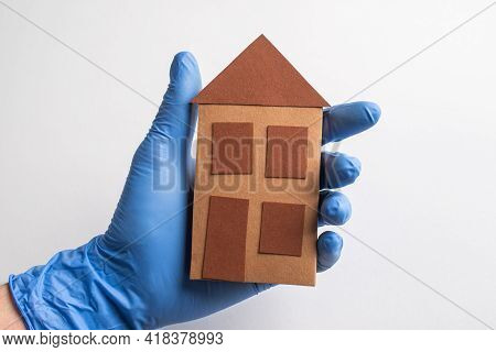 Hand In Glove Holding A Paper House On White Background