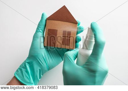 Hands In Gloves Spraying Disinfectant Onto A Paper House