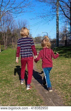 Children Walking In The Park In Spring. Siblings Holding Hands