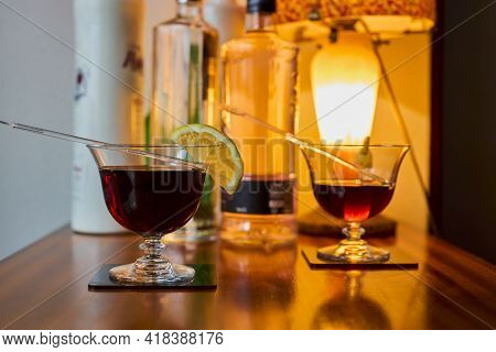 Cocktail Glasses With Vermouth And Lemon, And Various Bottles