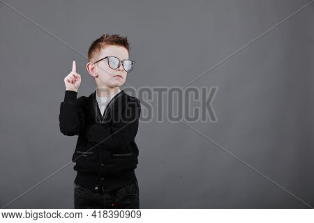 Portrait Of Stylish Little Boy With Finger Pointed Up. Little Child In Glasses Has Idea. Kid Isolate