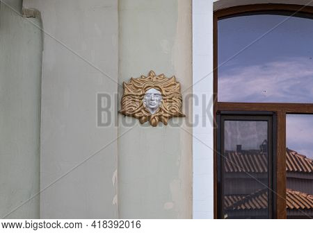Bas-relief Female Face With Hair On The Wall Of The Facade Of An Ancient Building