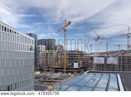 Oslo, Norway - July 2018:  Tall Cranes And Scaffolding Under The Blue Sky. Completed Modern Building