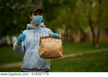 Girl Courier In A Medical Mask And Medical Gloves On Street. Young Woman Food Delivery Worker. Deliv