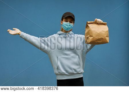 Girl Courier In A Medical Mask And Medical Gloves On Blue Background. Delivery Service In Quarantine