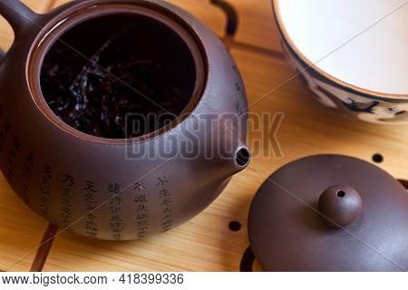 Handmade Purple Yixing Clay Chinese Teapot With Shu Pu Erh And Porcelain Bowl On Bamboo Teaboard Tea